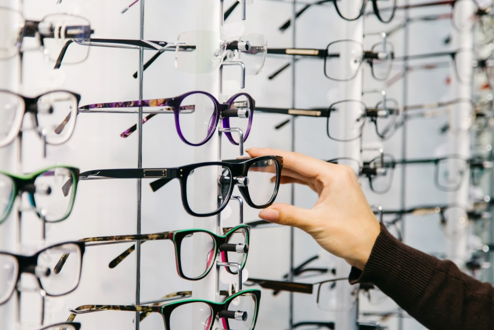 A close look at various reading glasses on display on racks.