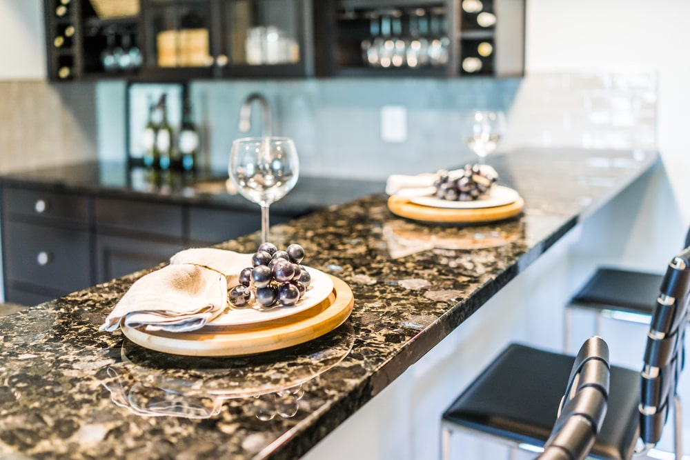 A close look at a breakfast bar with dark granite countertop.