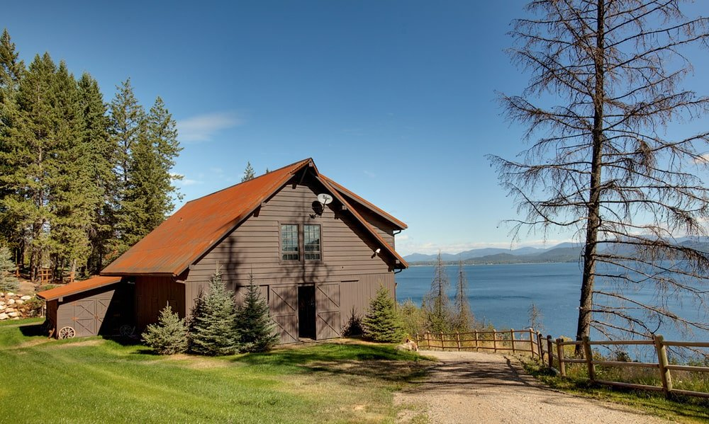 This is the separate wooden structure that serves as a barn. It has dark brown exterior walls that stand out against the surrounding green landscape and the view of the lake. Image courtesy of Toptenrealestatedeals.com.