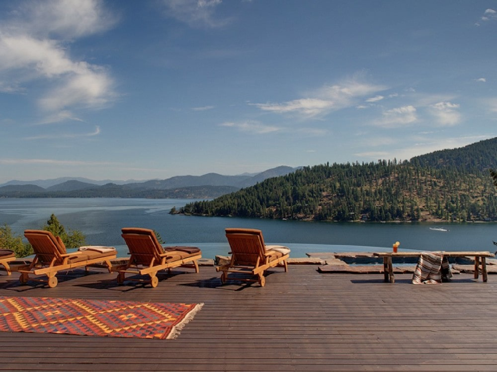 This is the deck of the back of the house with a few lawn chairs facing the infinity edge pool at the far end with a sweeping view of the lake below. Image courtesy of Toptenrealestatedeals.com.