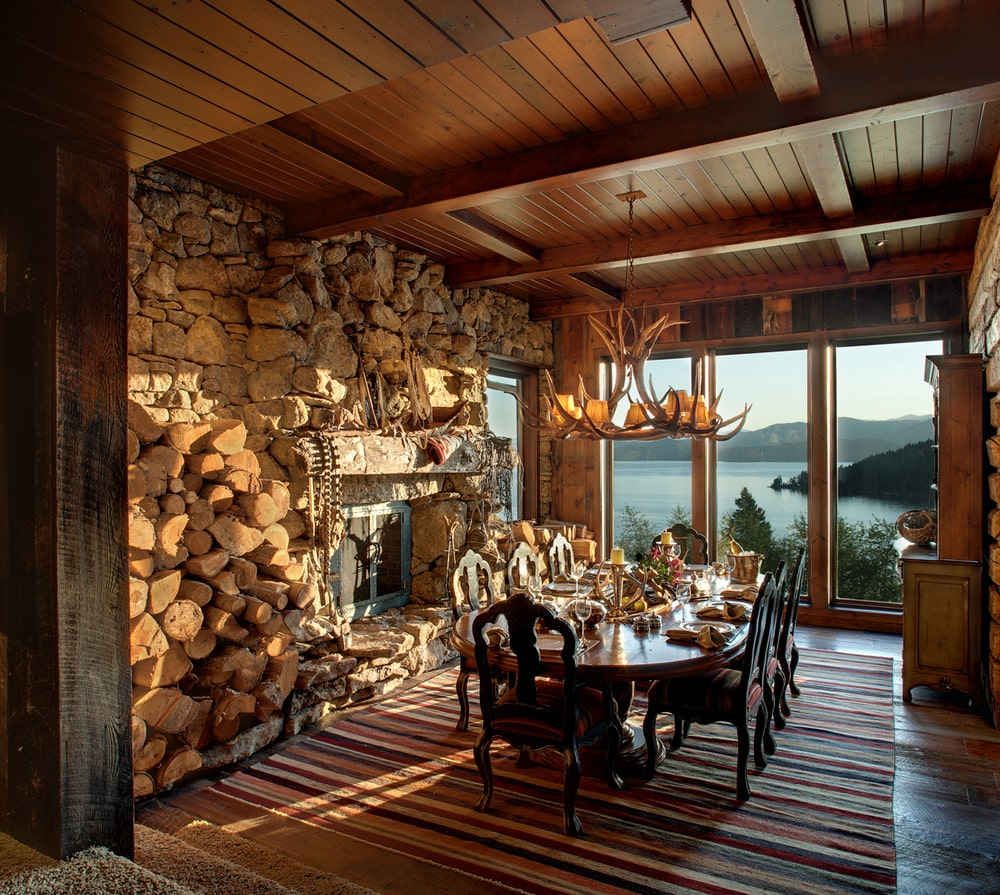 The formal dining area has a large dining table topped with an antler chandelier from a wooden coffered ceiling. These are then complemented by the glass wall and the stone fireplace that dominates an entire wall. Image courtesy of Toptenrealestatedeals.com.