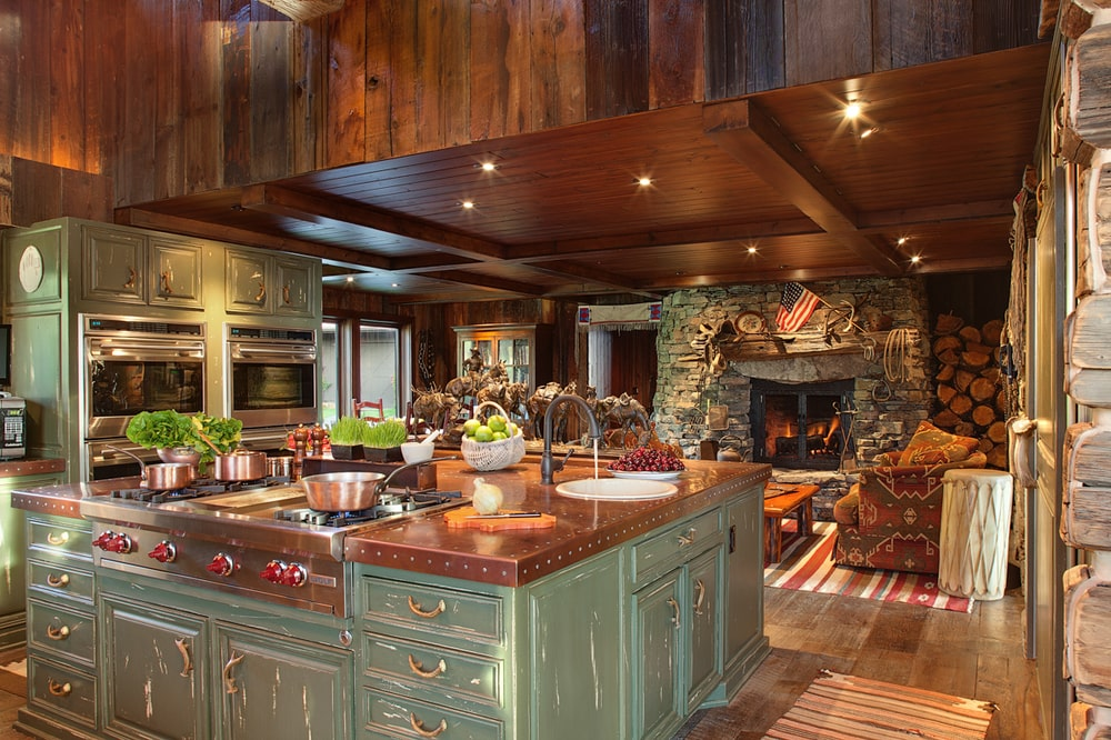The kitchen has a large kitchen island in the middle with a green tinge to its cabinetry complemented by a butcher block countertop that matches the tone of the ceiling and the hardwood flooring. Image courtesy of Toptenrealestatedeals.com.