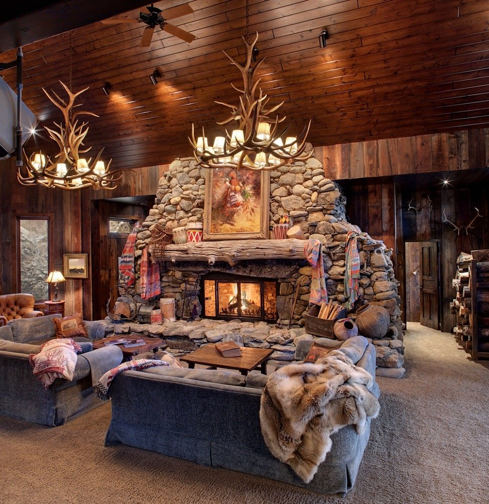 This is the living room with a large stone structure housing the fireplace across from the sofa that is topped with a couple of antler chandeliers hanging from a tall wooden ceiling. Image courtesy of Toptenrealestatedeals.com.