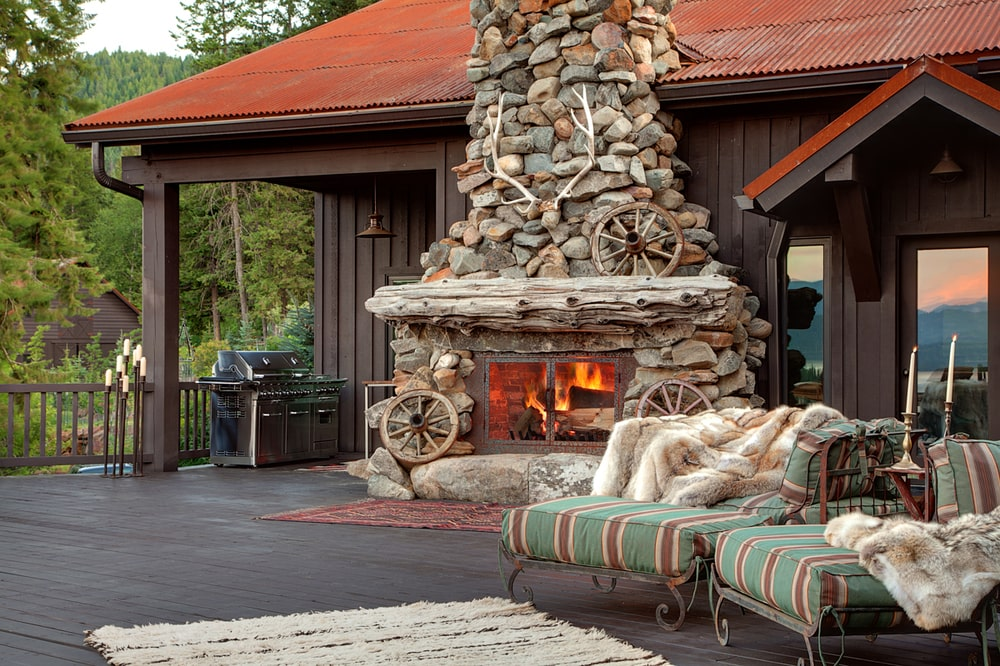 This is a look at the patio deck of the house with a large rustic stone outdoor fireplace to warm the cushioned lounge chairs on the wooden flooring. Image courtesy of Toptenrealestatedeals.com.