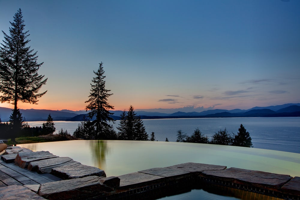 This is the infinity edge pool at the back of the house with a sweeping view of the lake below along with silhouettes of trees. Image courtesy of Toptenrealestatedeals.com.