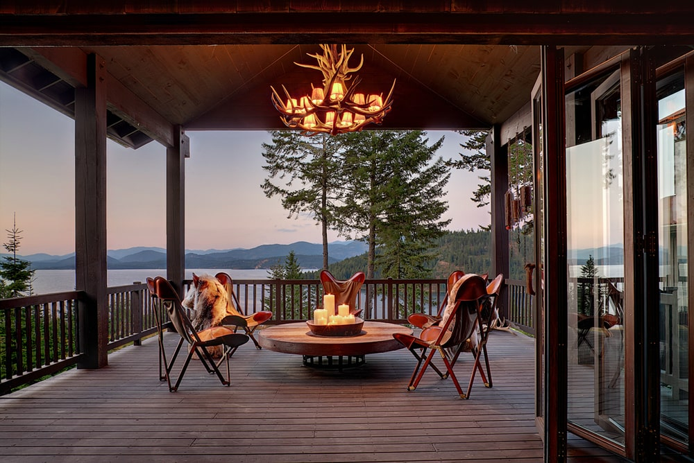 This is the terrace fitted with a set of chairs surrounding a wooden coffee table topped with an antler chandelier from a wooden cathedral ceiling. Image courtesy of Toptenrealestatedeals.com.