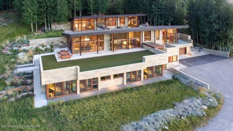 This is an aerial view of the back of the house with an abundance of glass walls facing the sweeping view of the valley. These are complemented by the grass lawns and surrounding tall trees. Image courtesy of Toptenrealestatedeals.com.