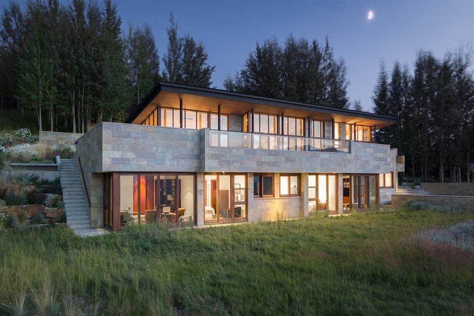 This is a look at the back of the house showcasing the large glass walls that glow warmly from the interior lights. Image courtesy of Toptenrealestatedeals.com.