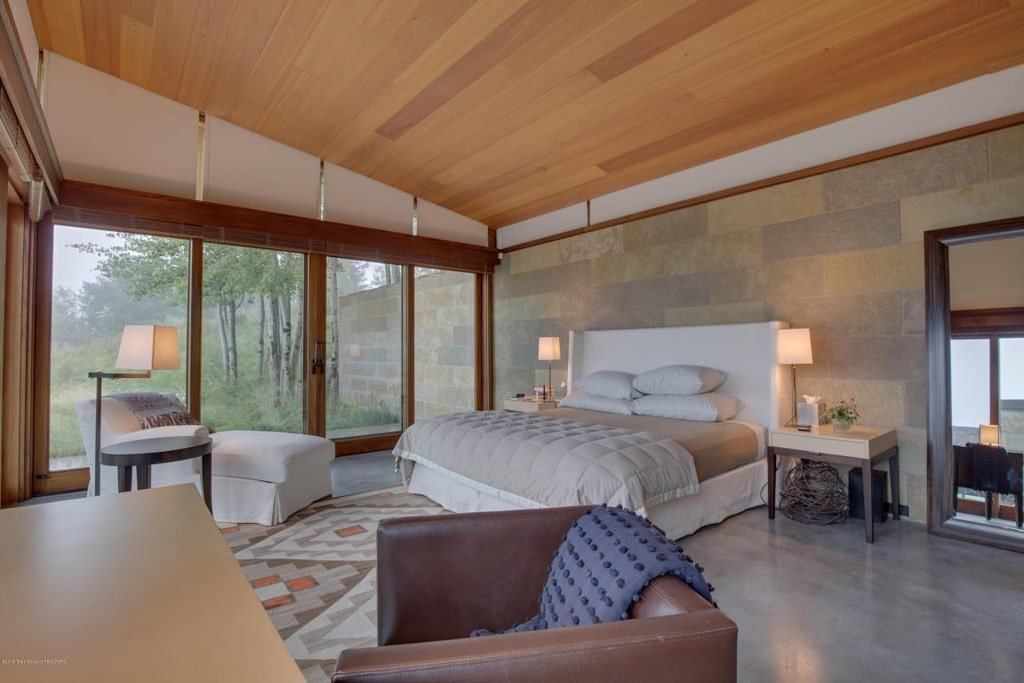 This is the bedroom with a wooden shed ceiling and a light gray bed with a cushioned headboard flanked by table lamps. Image courtesy of Toptenrealestatedeals.com.