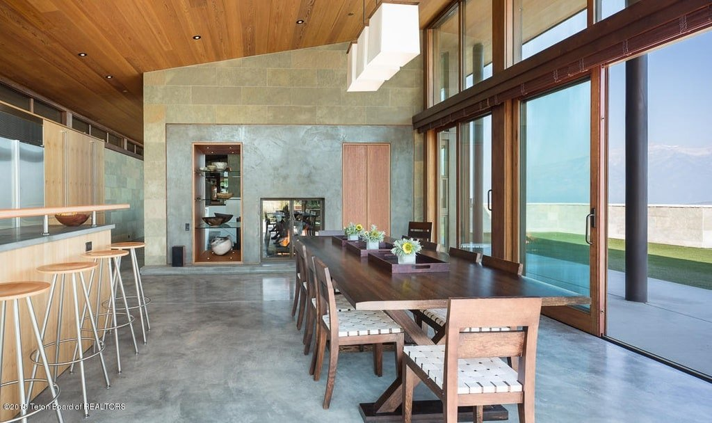 This is the dining area beside the kitchen with a row of pendant lights hanging from the tall shed ceiling with a wooden tone. Image courtesy of Toptenrealestatedeals.com.