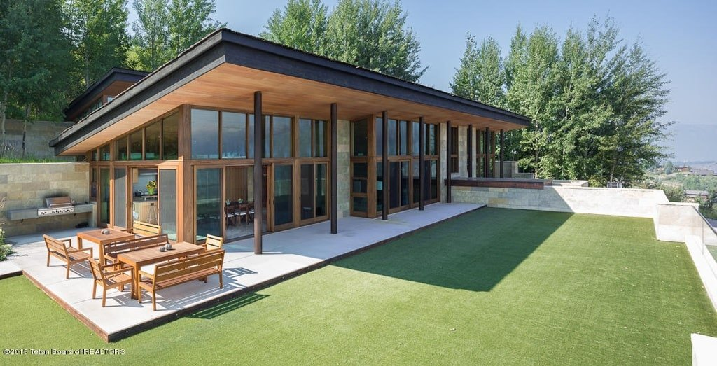 This is a close look at the guest level of the house with glass walls and an artificial grass lawn with a porch. Image courtesy of Toptenrealestatedeals.com.