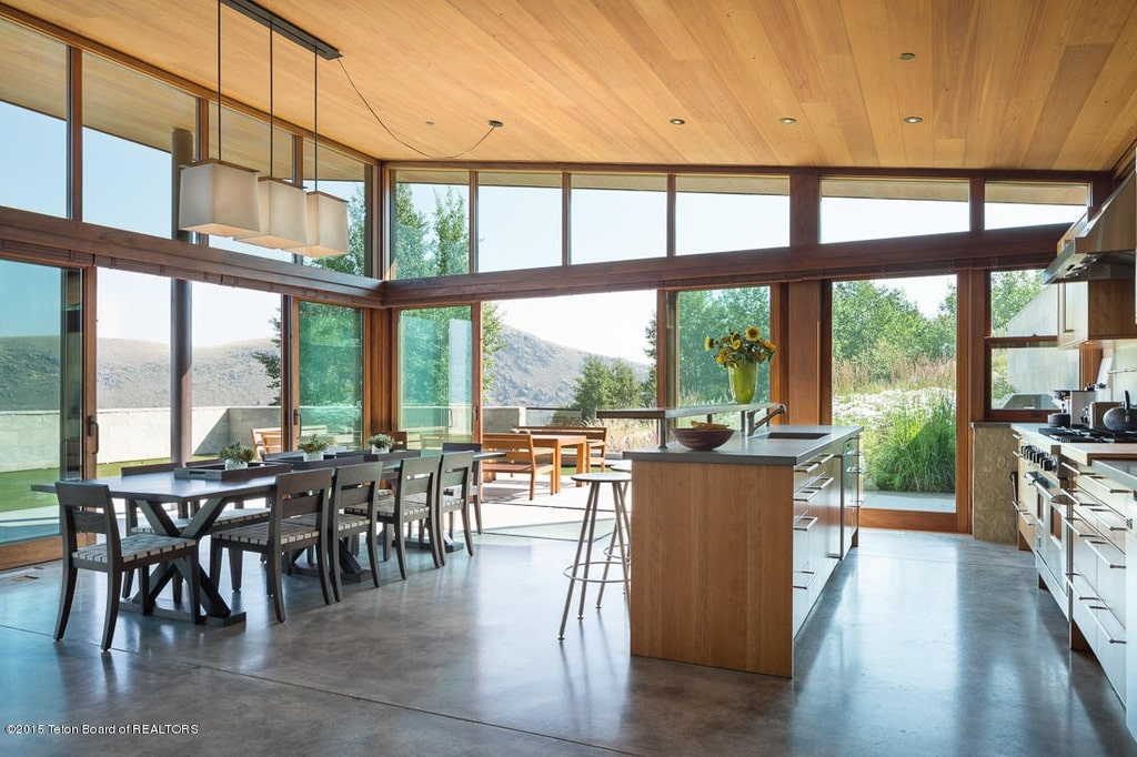 This view of the kitchen and dining area shows the tall shed ceiling and the kitchen island with a matching wooden cabinetry. Image courtesy of Toptenrealestatedeals.com.