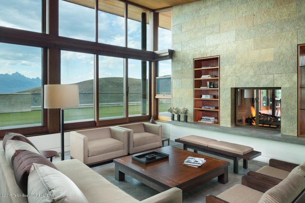 This is the living room with a large glass wall that lets in natural lighting. This is paired with a soaring wooden ceiling. lImage courtesy of Toptenrealestatedeals.com.