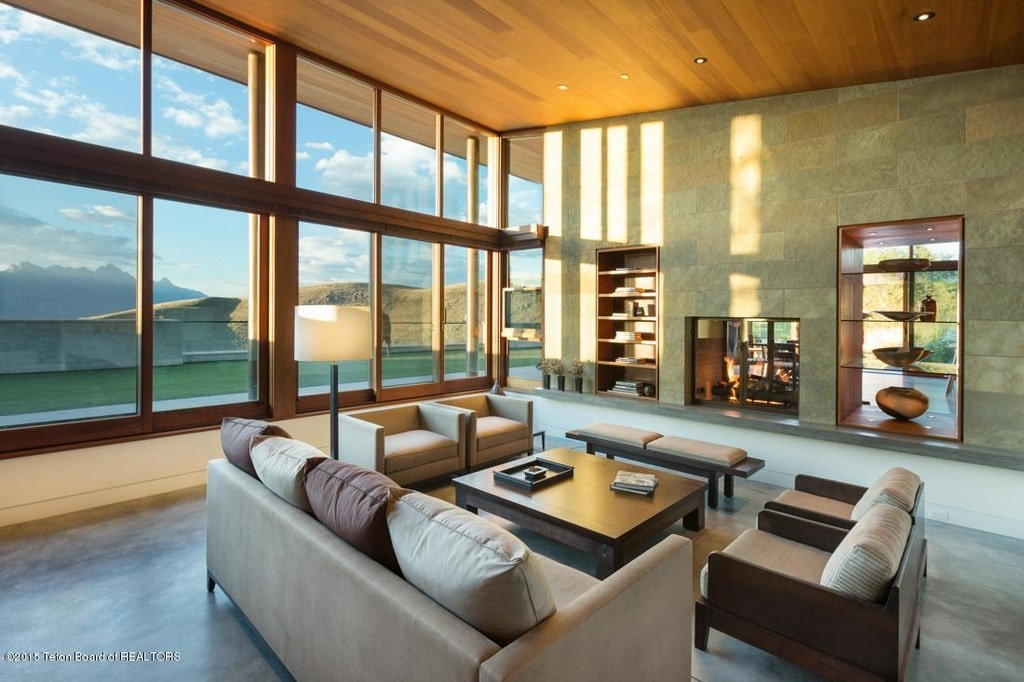 This other look at the living room showcases the gray sofa set paired with a wooden coffee table across from the two-way fireplace. Image courtesy of Toptenrealestatedeals.com.
