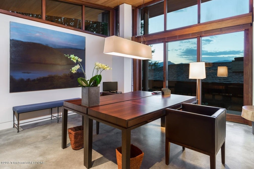 This is the two-person home office with a large dark wooden desk topped with a large pendant light complemented by the glass wall on the side. Image courtesy of Toptenrealestatedeals.com.