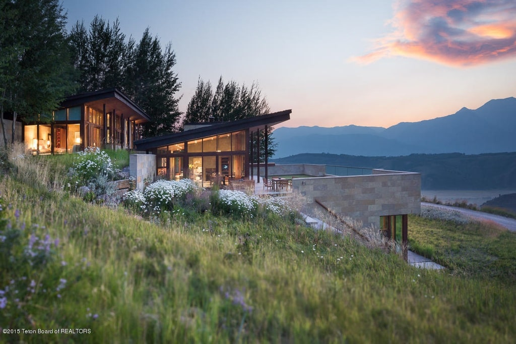 This is a side view of the contemporary-style home showcasing the glass walls glowing with yellow lights and the sweeping view of the valley below. Image courtesy of Toptenrealestatedeals.com.