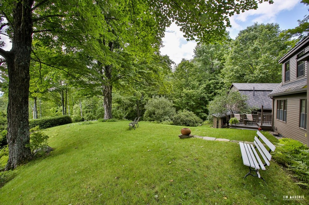 Just outside the wall of the house is a wooden park bench placed on the spacious grass lawn. Image courtesy of Toptenrealestatedeals.com.