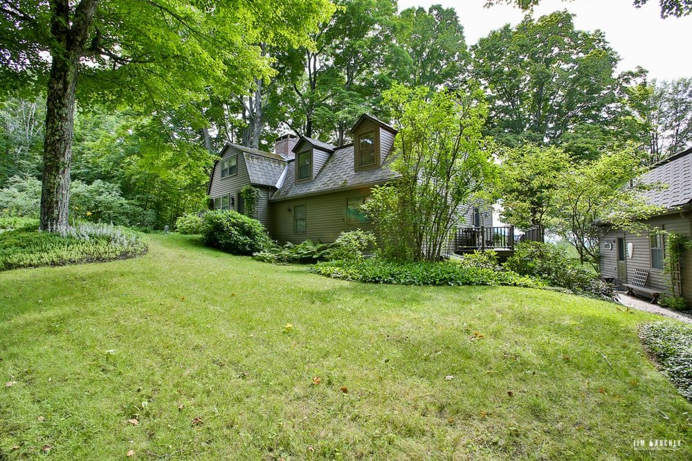 This is an external look at the house showcasing the dark exterior wall tone that cnontrasts with the vibrant green tones of the surrounding foliage. Image courtesy of Toptenrealestatedeals.com.