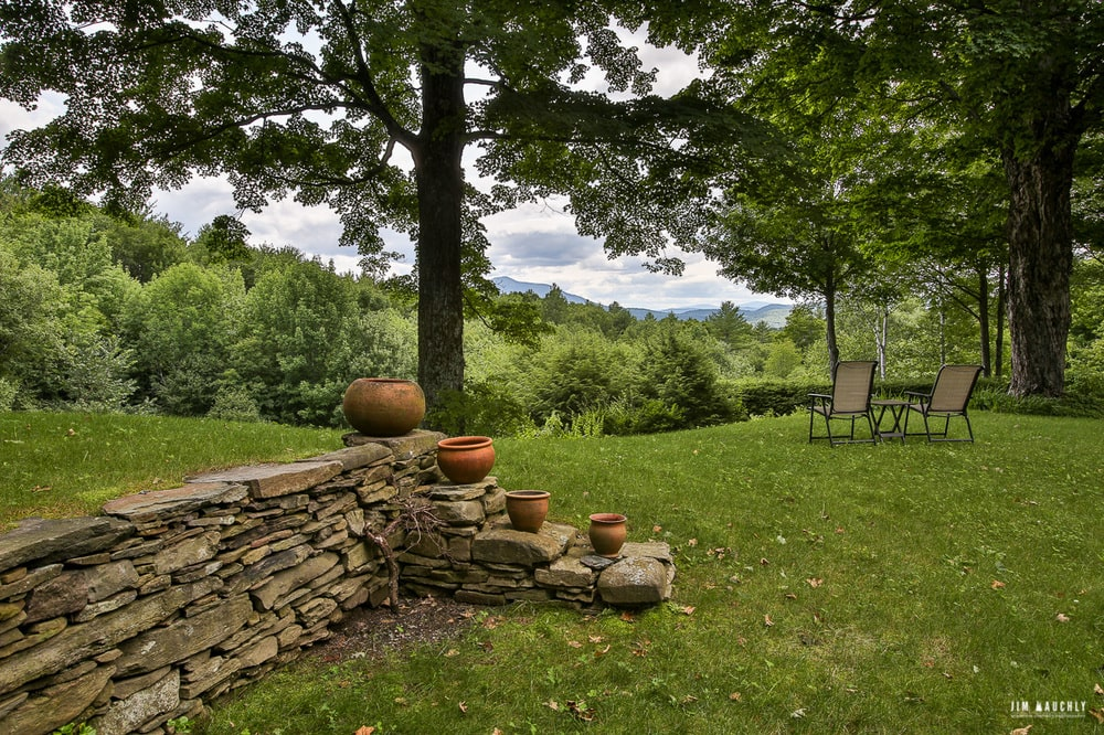 This part of the landscape also has a low stone wall with a set of steps adorned by different-sized clay pots. Image courtesy of Toptenrealestatedeals.com.