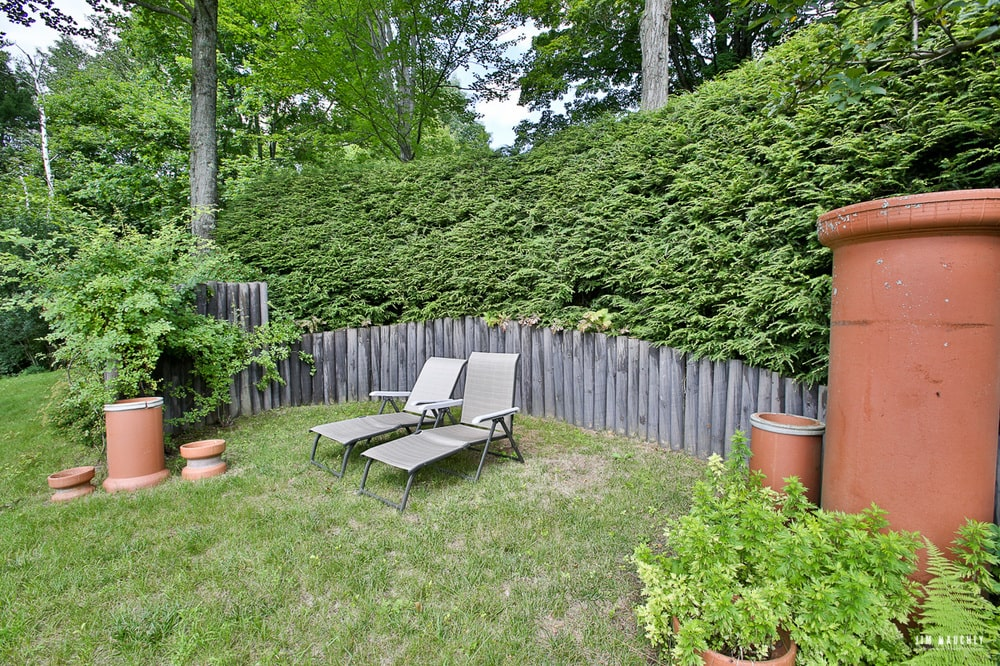This is a look at another grass lawn fitted with a couple of lawn chairs surrounded by a low stone wall, potted plants and shrubs. Image courtesy of Toptenrealestatedeals.com.