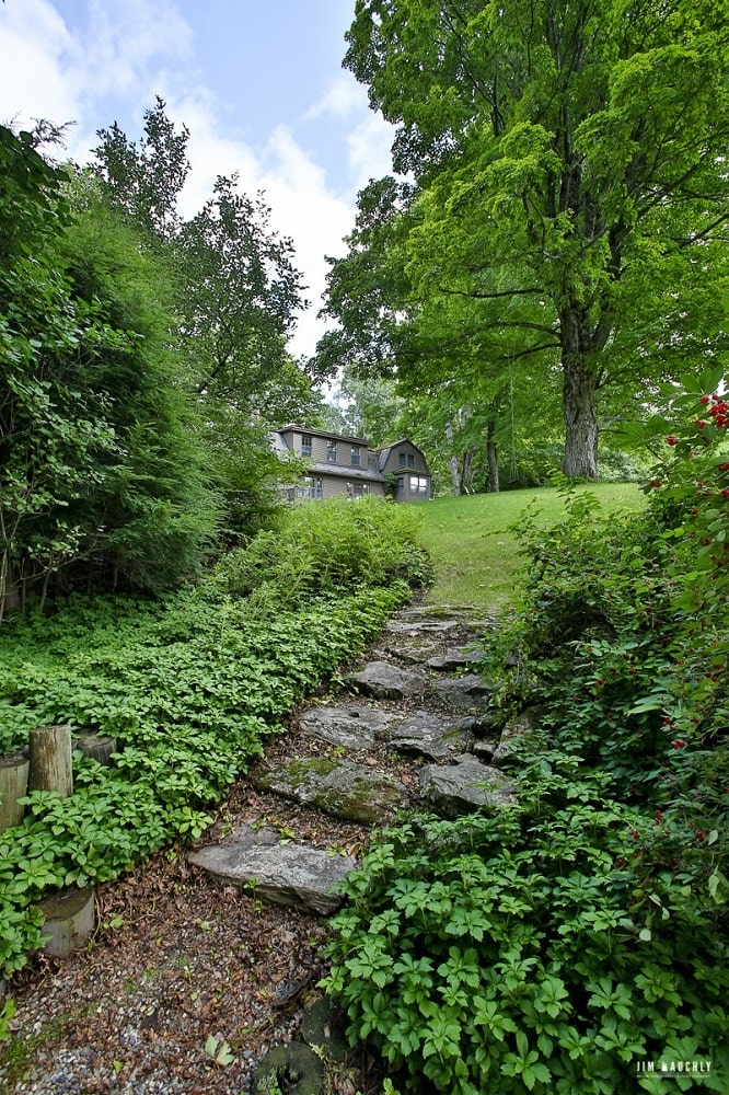This part of the grounds showcase the embedded stone slabs to form a walkway from the grass lawn. Image courtesy of Toptenrealestatedeals.com.