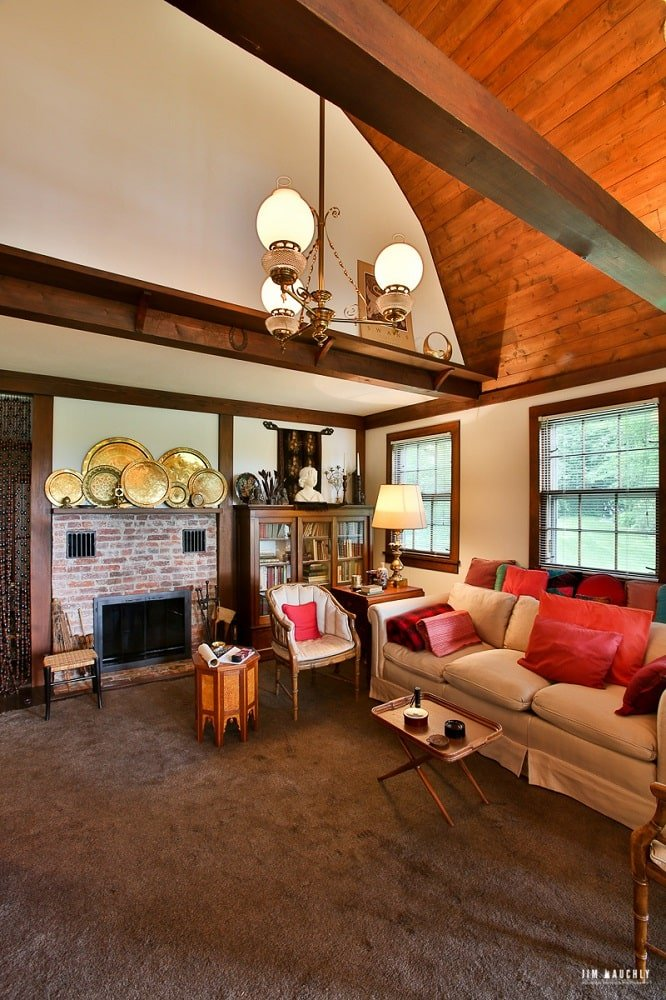 This is the living room of the house with a tall wooden ceiling, a chandelier, a beige sofa and a a red brick fireplace topped with decorative plates on display. Image courtesy of Toptenrealestatedeals.com.