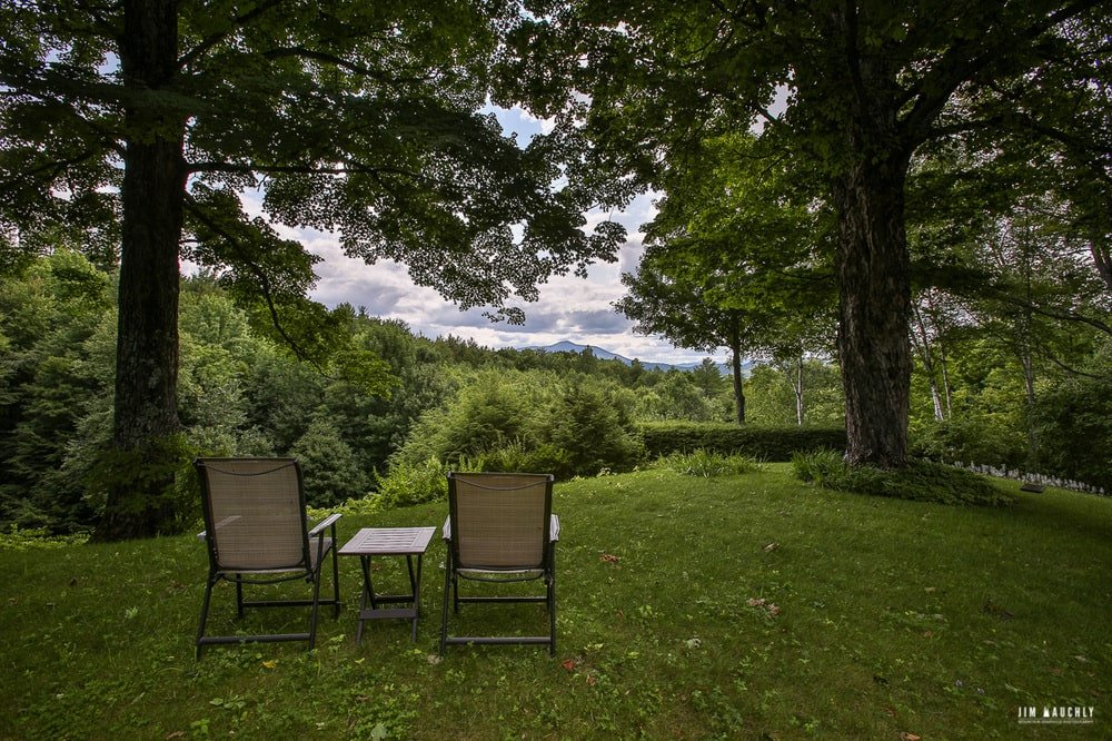 This is a look at the grass lawn where two lawn chairs are placed along with a small side table. This is complemented by the canopy of tall trees and the sweeping view of the landscape. Image courtesy of Toptenrealestatedeals.com.