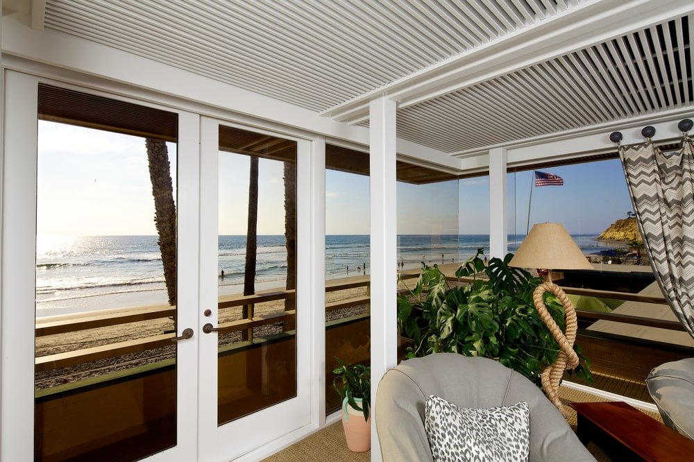 This is a closer look at the balcony door of the bedroom adorned with a potted plant at the corner behind the armchair and standing lamp. Image courtesy of Toptenrealestatedeals.com.