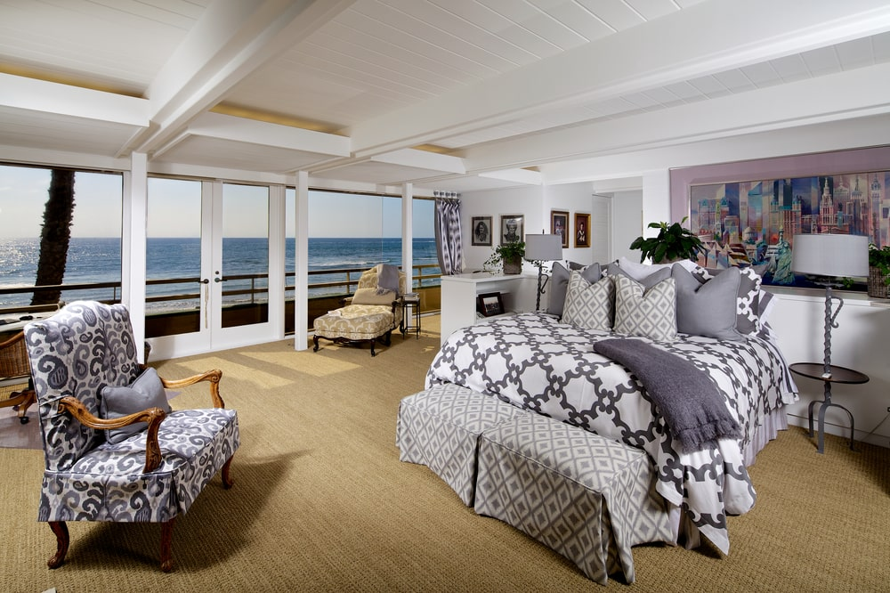 This is the spacious primary bedroom with a gray bed, white tray ceiling and a set of glass doors that open the bedroom to the balcony that overlooks the ocean. Image courtesy of Toptenrealestatedeals.com.