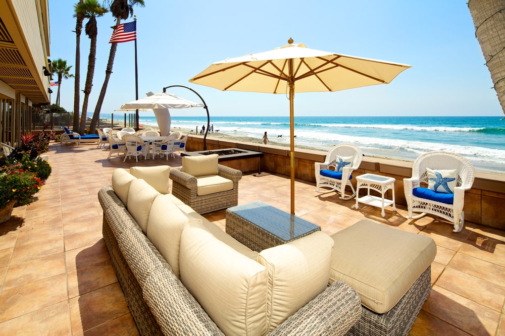 This is the spacious entertainment deck with a beige tiled flooring, a sofa set and a couple of dining areas on the far side. Image courtesy of Toptenrealestatedeals.com.