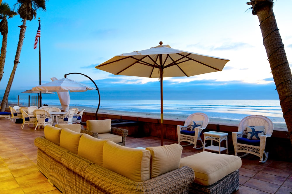 This is a sunset view of the entertainment deck that has a woven wicker sofa set facing the ledge overlooking the ocean. Image courtesy of Toptenrealestatedeals.com.
