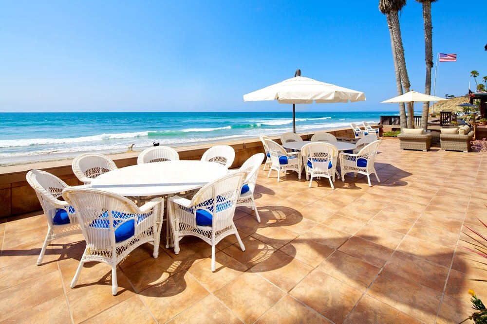 This is a view of the large entertainment deck with a couple of outdoor dining sets with a sweeping view of the ocean waves. Image courtesy of Toptenrealestatedeals.com.