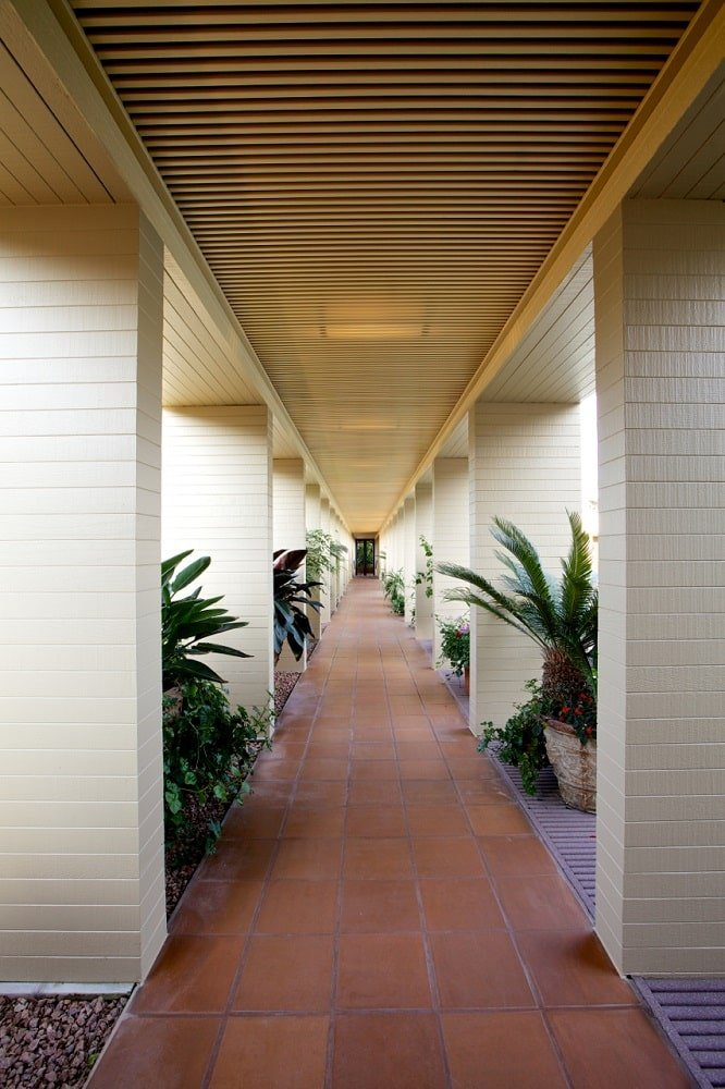 This is a look at the hallway on the side of the pool with terracotta flooring tiles, beige pillars and potted plants in between. Image courtesy of Toptenrealestatedeals.com.