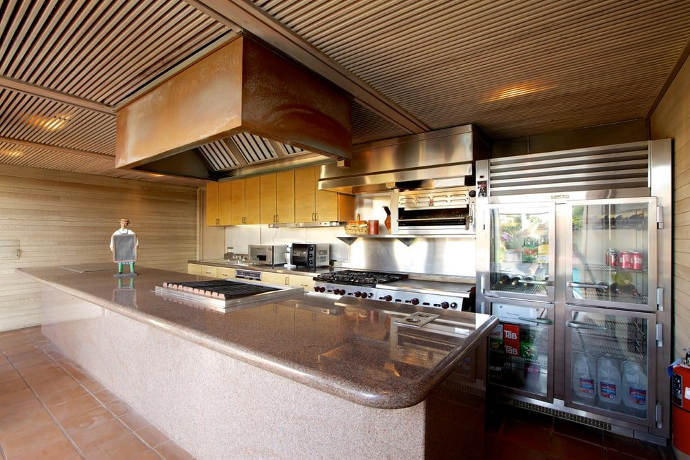 This is a look at one of the kitchens with a large kitchen island underneath a wooden ceiling. Across from this is the cabinetry that is dominated by the stainless steel appliances. Image courtesy of Toptenrealestatedeals.com.