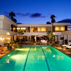 This is a nighttime view of the mansion from the vantage of the swimming pool. This is located in the middle of the square-shaped mansion that has glass walls that glow along with the exterior lights and the pool. Image courtesy of Toptenrealestatedeals.com.