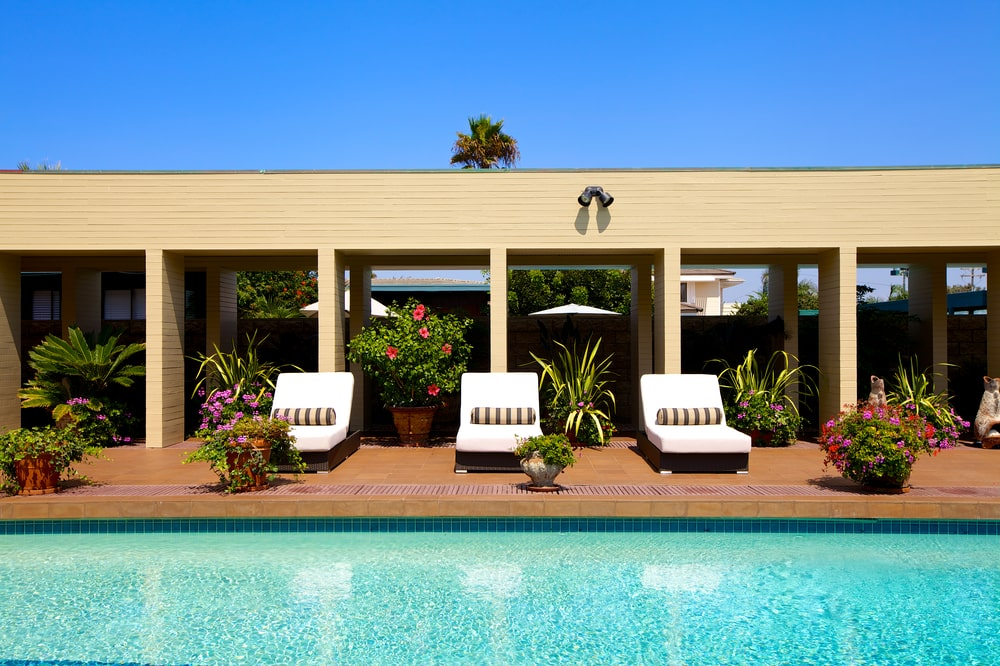 This is a closer look at the side of the pool lined with comfortable lawn chairs adorned by various potted plants. Image courtesy of Toptenrealestatedeals.com.