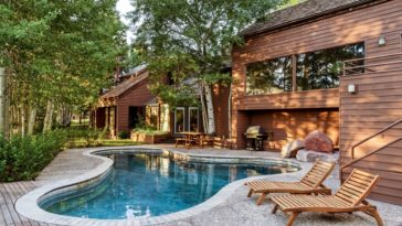 This is a view of the back of the mountain home with dark wooden exterior walls and large glass windows that are complemented by the surrounding tall trees and the large free-form pool. Image courtesy of Toptenrealestatedeals.com.