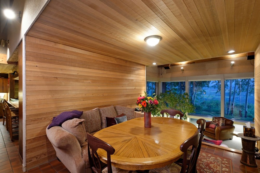 This other dining area is more like a breakfast nook with a sofa, a small wooden table and a couple of wooden chairs complemented by the wooden walls and ceiling. Image courtesy of Toptenrealestatedeals.com.