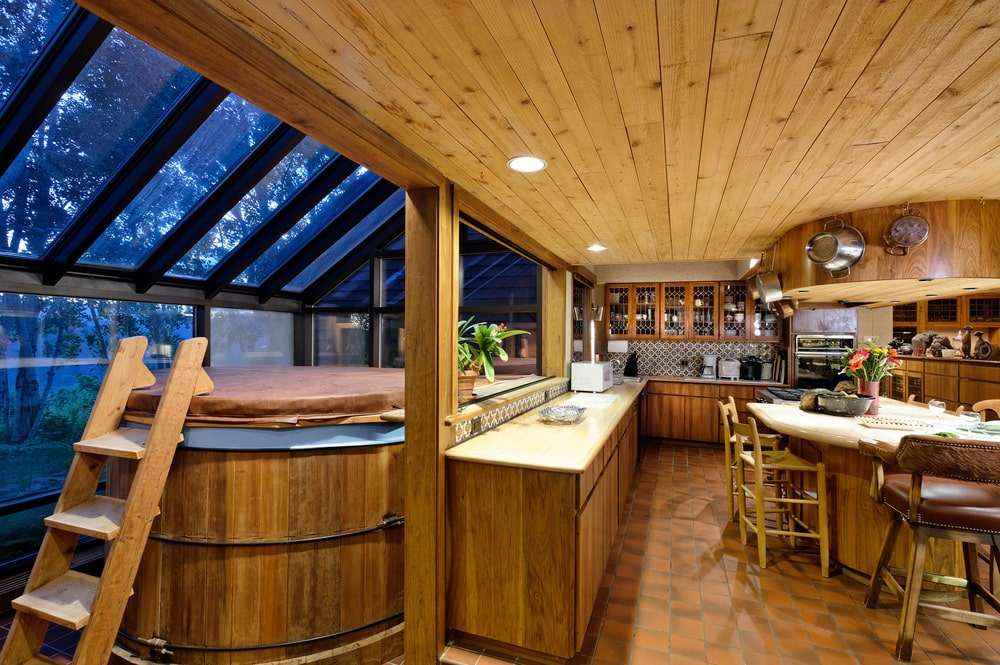 The spacious kitchen has wooden cabinetry that matches the ceiling. It also has a kitchen island and an L-shaped peninsula with wooden pillars and attached to a wooden hot tub. Image courtesy of Toptenrealestatedeals.com.