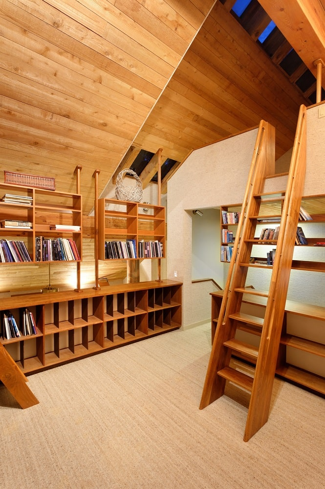 The library has built-in wooden bookshelves that match the tone of the wooden arched ceiling and the wooden ladder that leads to the reading nook. Image courtesy of Toptenrealestatedeals.com.