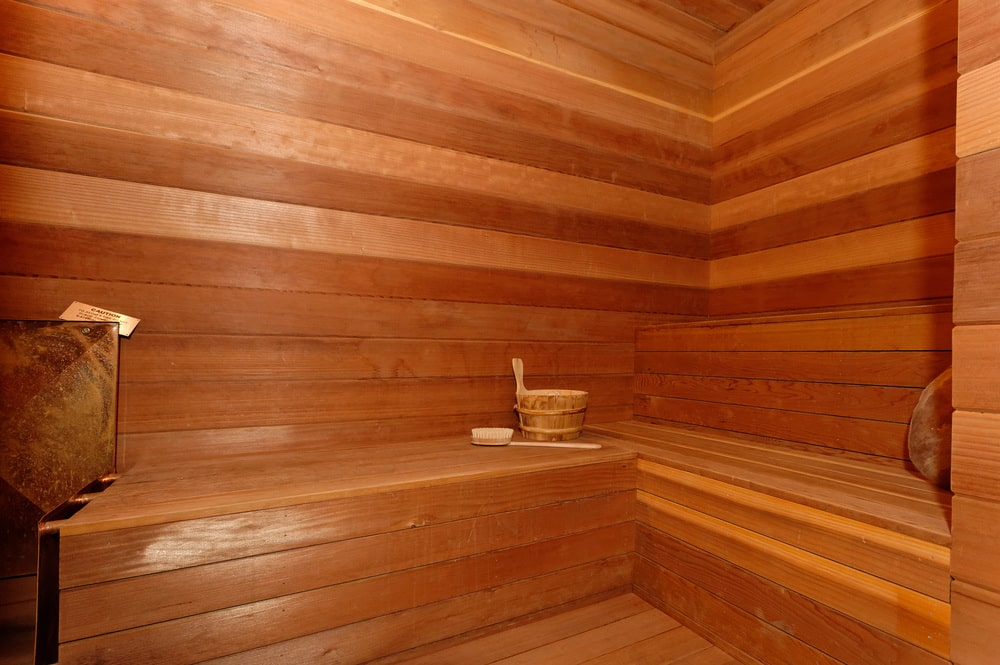 This is a close look at the steam room and sauna of the house with consistent wooden walls, floor and a built-in wooden bench lining the walls. Image courtesy of Toptenrealestatedeals.com.