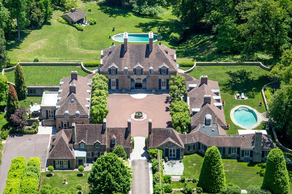 This is an aerial view of the mansion focusing on the main house. You can see here the large courtyard and driveway in front, a small pool on the side and a larger one at the back in the middle of a large lawn. Image courtesy of Toptenrealestatedeals.com.