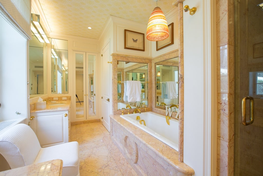 This bathroom has a bathtub housed in its own alcove with mirrors on the wall and a pendant light above to complement the beige tones. Image courtesy of Toptenrealestatedeals.com.