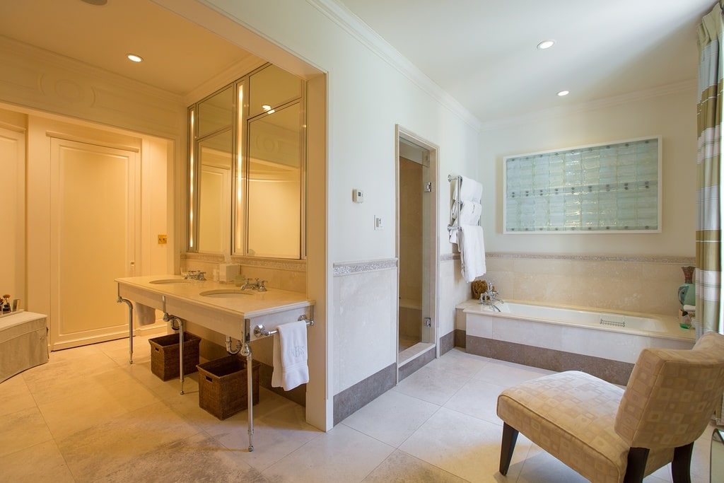 This other bathroom has a two-sink vanity around the corner from the bathtub and the entrance to the walk-in shower area. Image courtesy of Toptenrealestatedeals.com.