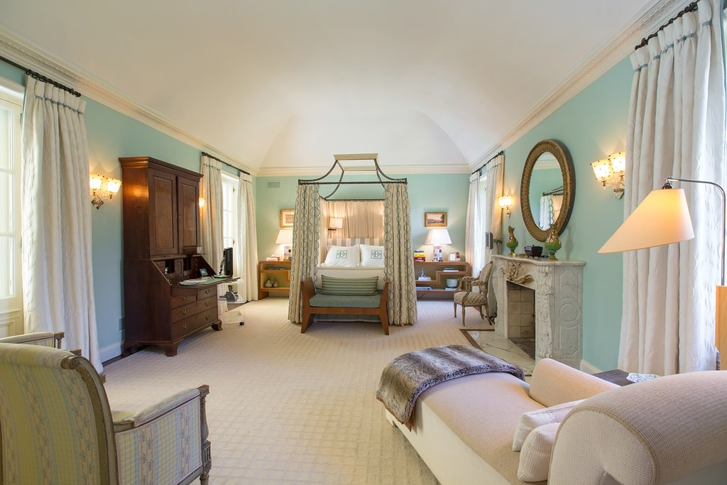 The primary bedroom has a fireplace with a marble mantle that stands out against the pastel tone of the walls. On the far side is the four-poster bed with curtains surrounded by wooden cabinets. Image courtesy of Toptenrealestatedeals.com.