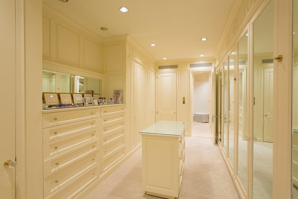The closet has a consisted bright beige tone to its cabinetry, walls, floor and ceiling. These are then complemented by the recessed lights with warm yellow light. Image courtesy of Toptenrealestatedeals.com.