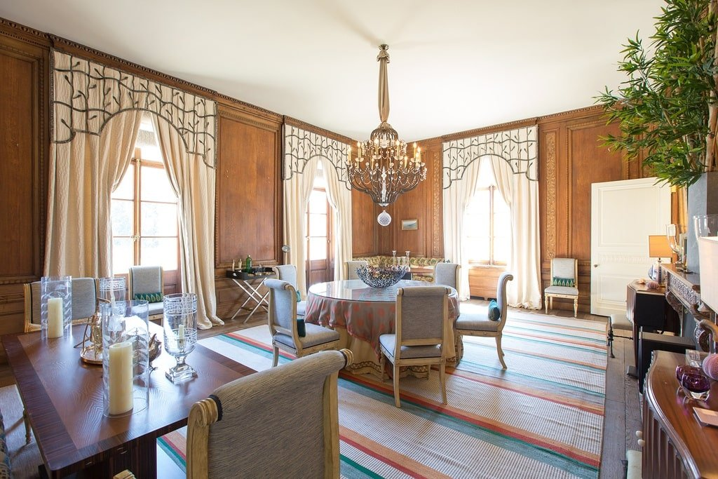 The dining area has a striped carpeted floor that has light pastel tones complemented by the tall windows and beige walls. Image courtesy of Toptenrealestatedeals.com.