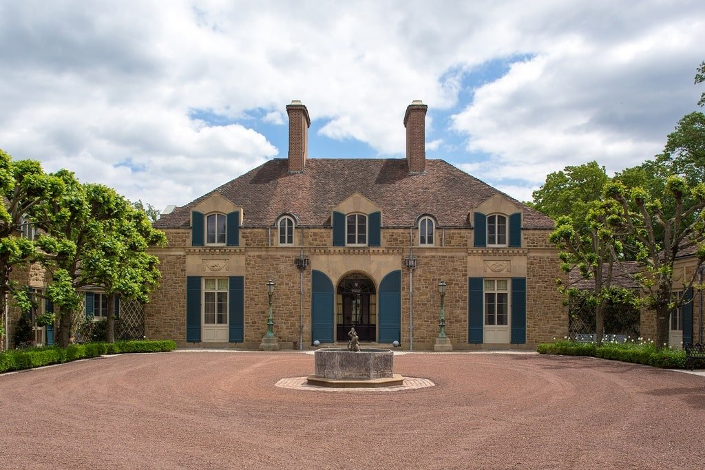 This is a front view of the mansion from the vantage of the large courtyard and driveway. It has a fountain in the middle that matches the earthy tone of the house exterior walls. Image courtesy of Toptenrealestatedeals.com.