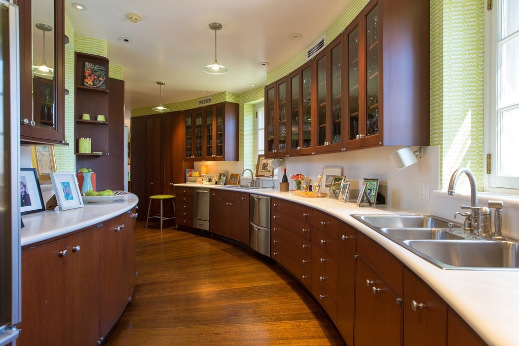 This is the other side of the kitchen with a curved long and narrow design. It has dark brown cabinetry lining the walls on both sides. Image courtesy of Toptenrealestatedeals.com.