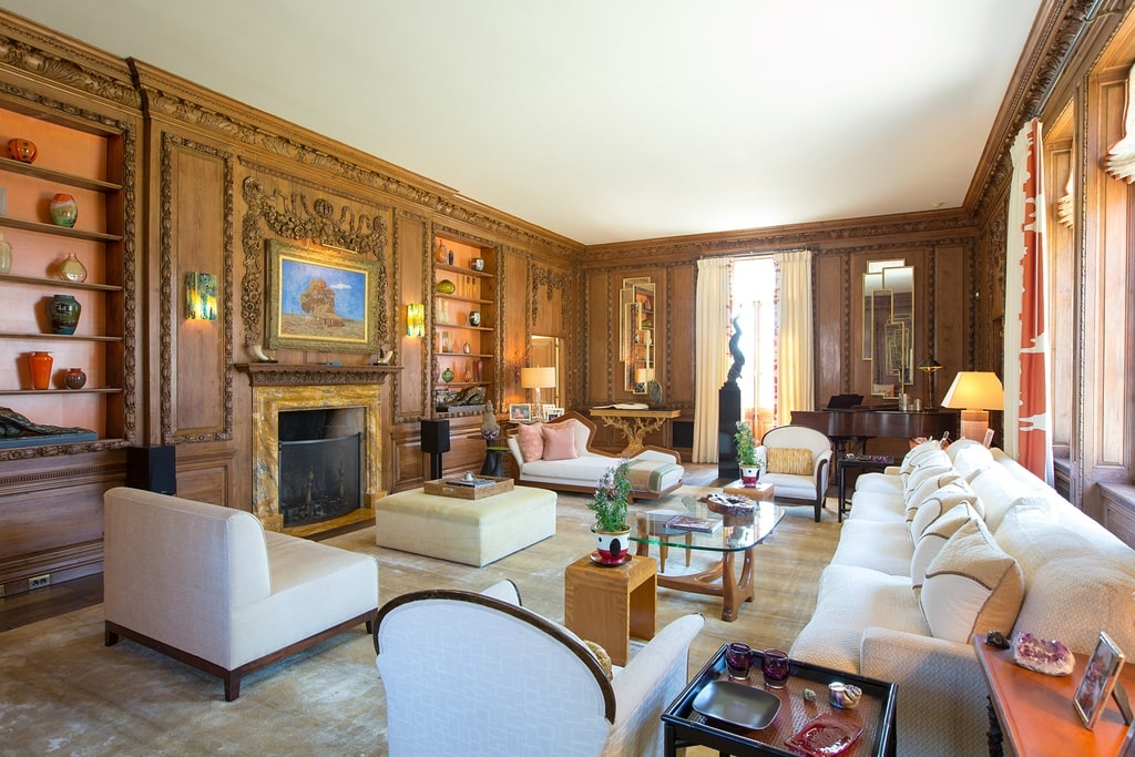 The formal living room has a fireplace with a wooden mantle that blends well with the walls. These are then contrasted by the bright tone of the sofa set that matches the ceiling. Image courtesy of Toptenrealestatedeals.com.